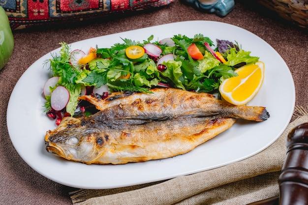 Vista frontal de pescado a la parrilla con una ensalada de verduras y hierbas con una rodaja de limón
