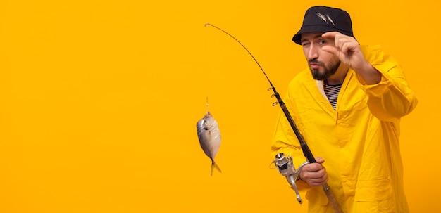 Vista frontal del pescador con caña de pescar con captura y espacio de copia