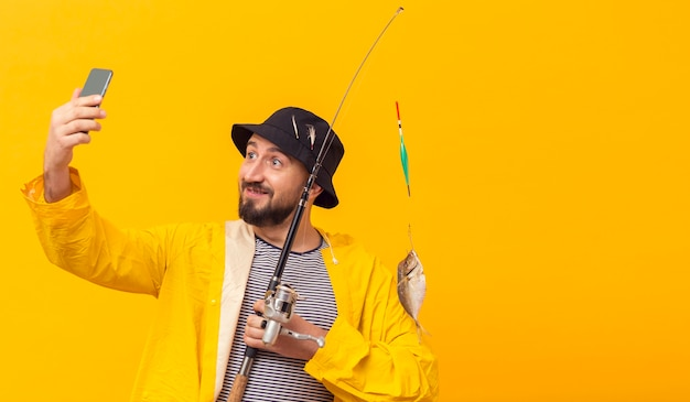 Vista frontal del pescador con caña de pescar y tomar selfie