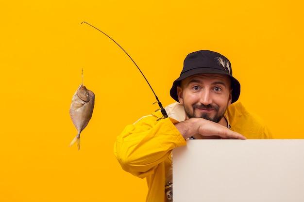 Vista frontal del pescador posando mientras sostiene la caña de pescar con captura