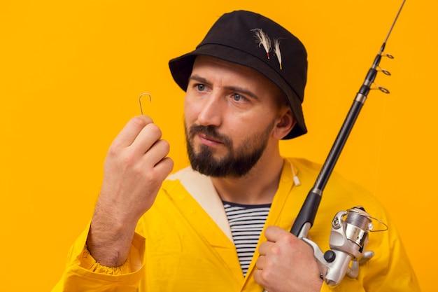 Vista frontal del pescador sosteniendo la caña de pescar y mirando el anzuelo