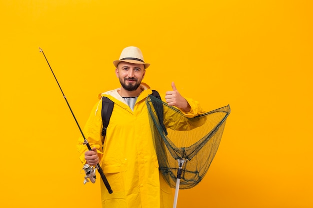 Vista frontal del pescador sosteniendo la red y dando pulgares arriba
