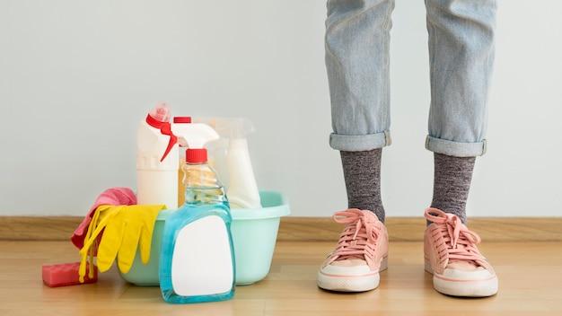 Vista frontal de las piernas con soluciones de limpieza y guantes.