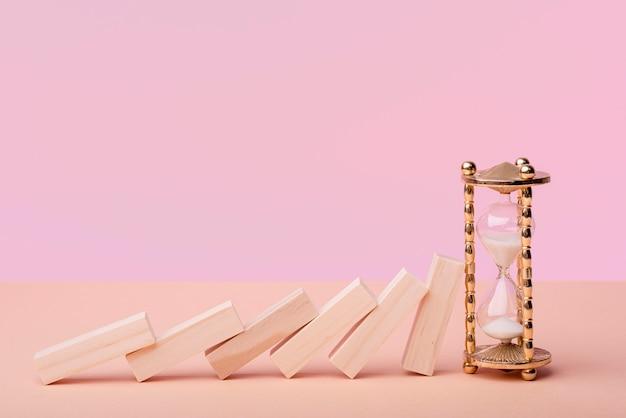 Vista frontal de piezas de dominó con reloj de arena.