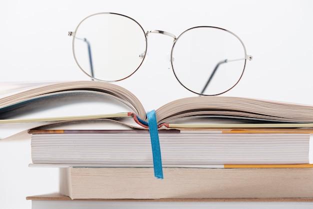 Vista frontal pila de libros con gafas en la parte superior