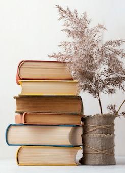 Vista frontal de la pila de libros con jarrón y flores.