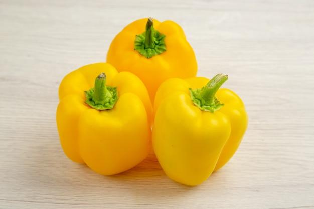 Vista frontal pimientos amarillos sobre fondo blanco árbol de ensalada comida de color picante maduro comida