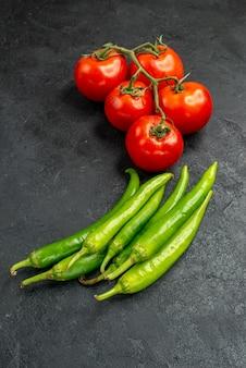 Vista frontal de pimientos picantes frescos con tomates rojos