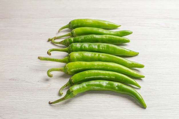 Vista frontal de pimientos picantes verdes sobre fondo blanco, ensalada madura y nerviosa caliente