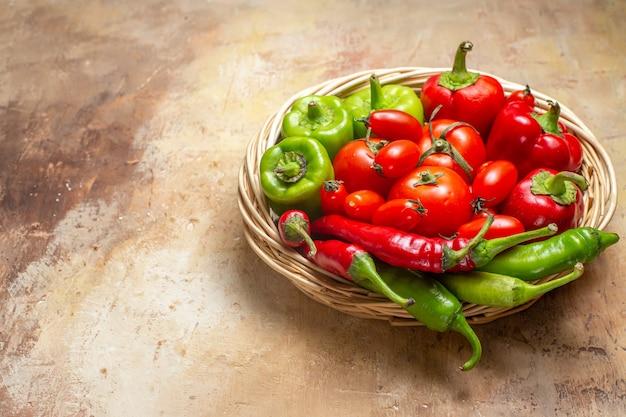 Vista frontal de pimientos verdes y rojos pimientos picantes tomates en canasta de mimbre sobre fondo ámbar lugar libre