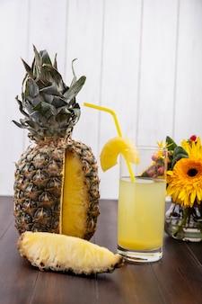Vista frontal de piña y rodaja de piña y jugo en vidrio con tubo para beber y flores sobre superficie de madera