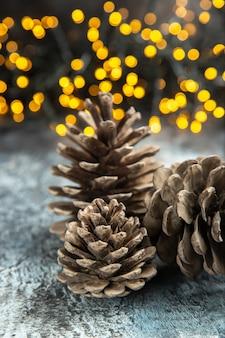 Vista frontal de piñas abiertas en luces de navidad de superficie oscura aislada