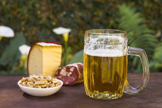 Vista frontal pinta con cerveza y aperitivos para beber