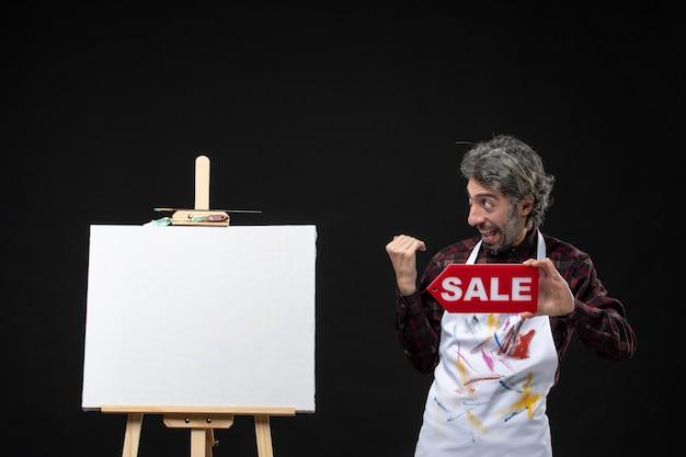 Vista frontal del pintor masculino con caballete sosteniendo pancarta de venta en la pared oscura