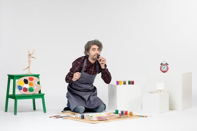 Vista frontal pintor masculino dibujando imágenes con pinturas en blanco imagen de trabajo artista color dibujar pintura arte