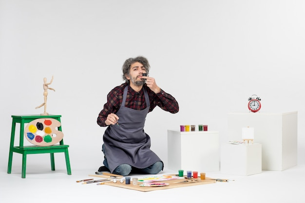 Vista frontal pintor masculino dibujar imágenes con pinturas en blanco imagen de trabajo artista dibujar pintura en color