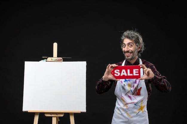 Vista frontal del pintor masculino sosteniendo banner de venta rojo en la pared oscura