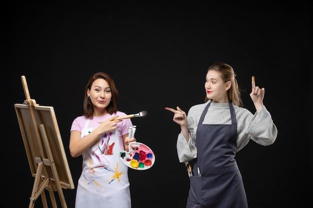 Vista frontal de la pintora dibujando en el caballete con otra mujer en la pared negra foto color arte imagen artista pinta trabajo