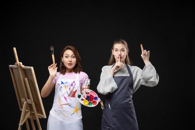 Vista frontal pintora dibujando en caballete con otra mujer en la pared negra foto color arte imagen artista trabajo de pintura