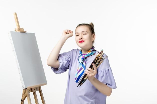Vista frontal pintora sosteniendo borlas para dibujar en la pared blanca imagen de mujer arte foto pintura dibujar artista lápiz caballete