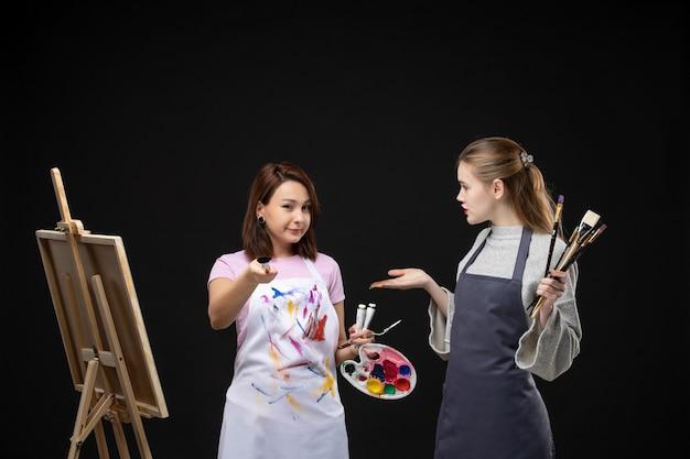 Vista frontal pintoras sosteniendo pinturas y borlas para dibujar en una pared negra dibujar trabajos de pintura cuadros de arte foto de color artista
