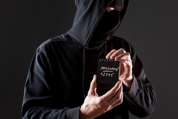 Vista frontal del pirata informático masculino que sostiene el cuaderno con contraseña