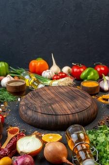 Vista frontal de la placa de madera redonda de cúrcuma en un tazón pequeño, cebolla verde, botella de aceite, pimiento verde, tomates en la mesa