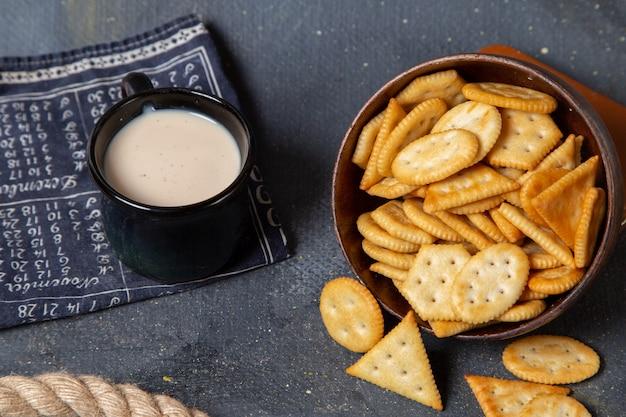 Vista frontal de la placa marrón con galletas saladas y patatas fritas junto con una taza de leche en la superficie gris