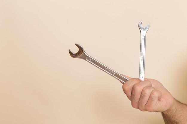 Vista frontal plata herramientas sostenidas por macho sobre fondo blanco herramienta instrumento macho