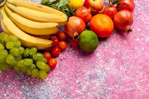 Vista frontal de plátanos frescos amarillos deliciosa fruta con uvas y granadas en el escritorio rosa