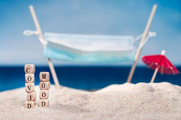 Vista frontal de la playa con sombrilla y humor covid