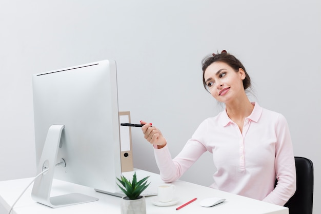 Vista frontal de la pluma encantadora mujer apuntando a la computadora