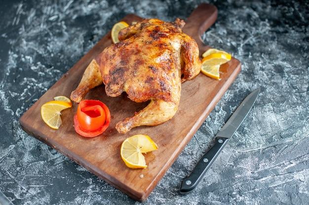 Vista frontal de pollo con especias cocidas con limón sobre carne gris claro, comida, plato de barbacoa, cena, pimienta, comida de color animal