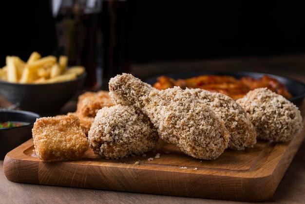 Vista frontal de pollo frito con papas fritas y bebida gaseosa