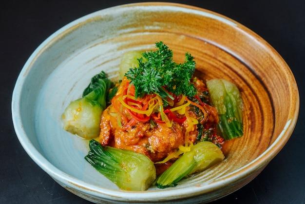 Vista frontal de pollo frito en salsa con puerro y hierbas en un plato