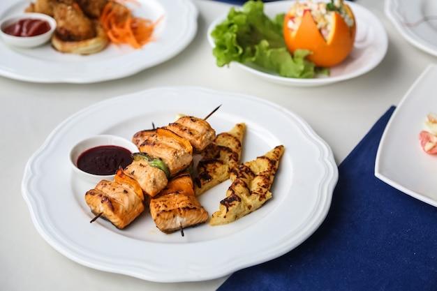 Vista frontal de pollo a la parrilla en brochetas con verduras y puré de papas en un plato con salsa