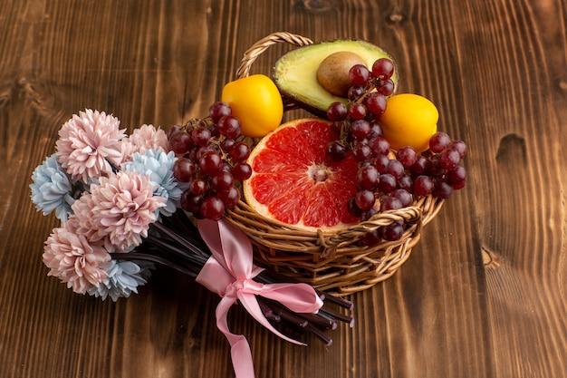 Vista frontal de pomelo fresco con flores sobre superficie de madera