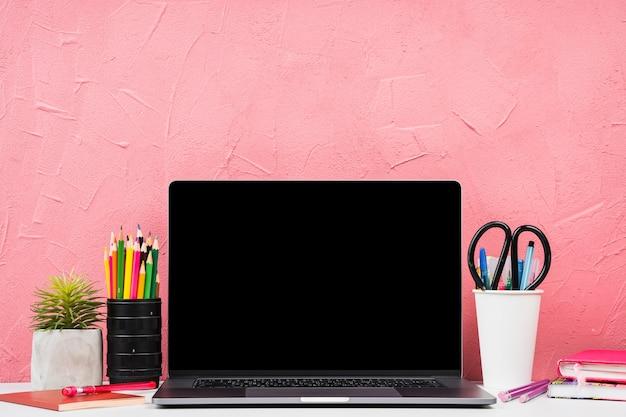 Vista frontal del portátil con elementos de papelería.
