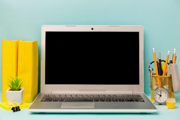 Vista frontal portátil con material de oficina en la mesa