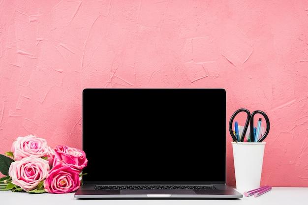 Vista frontal del portátil con ramo de rosas.