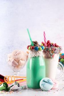 Vista frontal de postres con dulces coloridos y pajitas