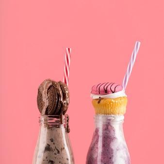 Vista frontal de postres con galletas y muffins con pajitas