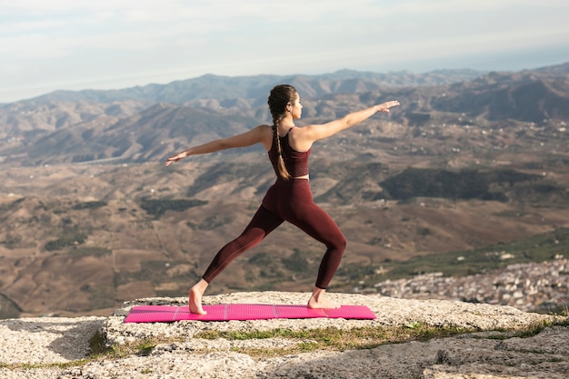 Vista frontal práctica de yoga al aire libre