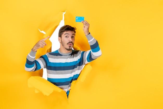 Vista frontal se preguntó joven sosteniendo una tarjeta mirando a través de la pared amarilla de papel rasgado