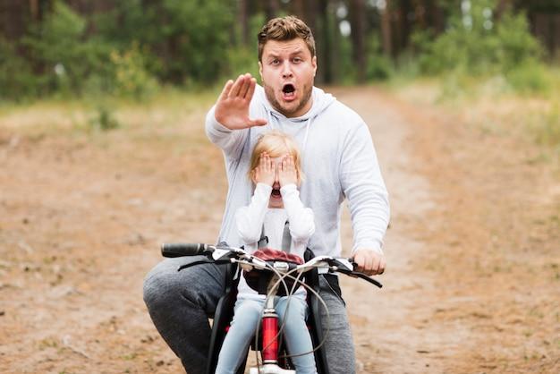 Vista frontal preocupado padre e hija en bicicleta