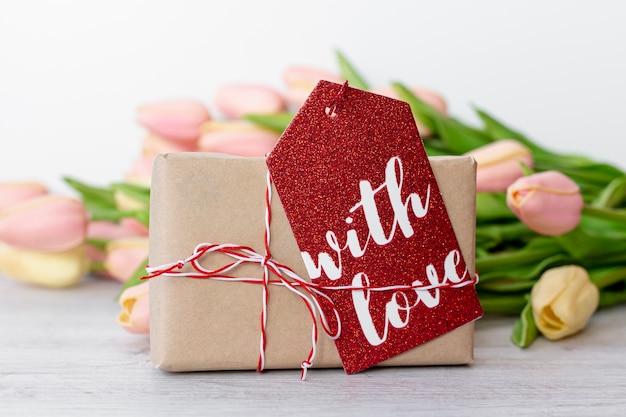 Vista frontal del presente con etiqueta y tulipanes para el día de san valentín