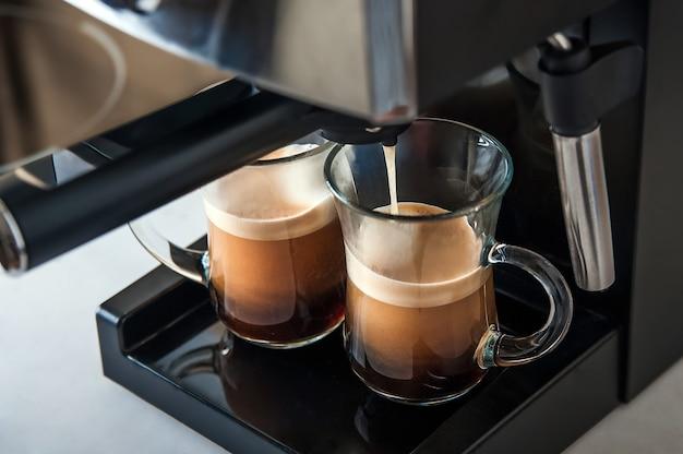 Vista frontal de primer plano de café de dos tazas transparentes. cafetera casera y proceso de elaboración de la bebida de café. copie el espacio.