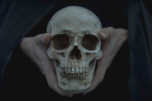 Vista frontal de primer plano del cráneo retenido por el hombre