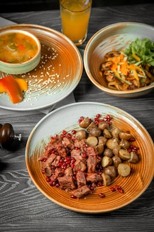 Vista frontal del primer segundo plato principal y ensaladas de sopa de carne con papas con un refresco sobre la mesa
