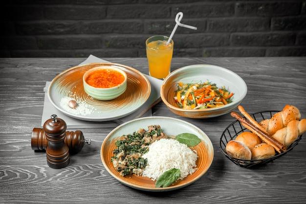 Vista frontal del primer segundo plato principal y sopa de lentejas ensalada de verduras y arroz con carne y jugo sobre la mesa